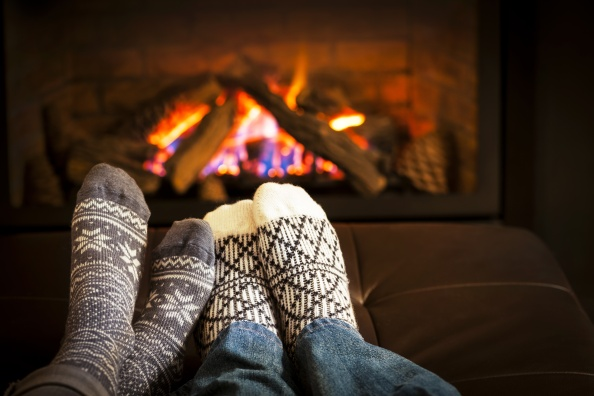 Feet in wool socks warming by cozy fire